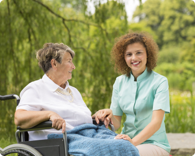 caregiver holding the hands and lap of elderly patient in a wheelchair