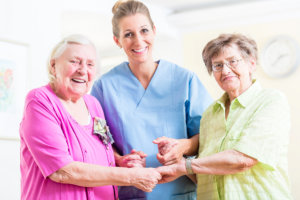 caregiver and elders holding each other