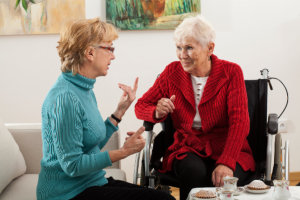 caregiver and old woman having a serious conversation