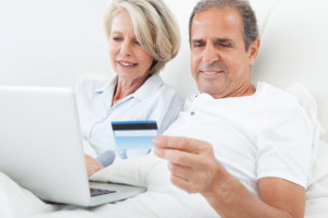old man holding electronic card while old woman broswing in internet using their laptop